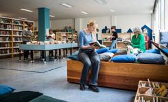 Lezende bezoekers in bibliotheek Vrede