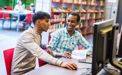 Twee bezoekers gebruiken een pc in bibliotheek Permeke