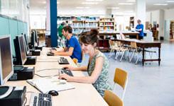Bezoekers gebruiken een computer in bibliotheek Vrede