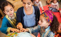 Kinderen kijken op de wereldbol tijdens een voorleesuurtje