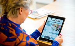 Bezoeker leest een Spaanse krant op een laptop van de bib