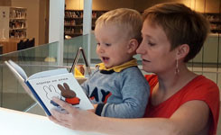 Moeder en kind lezen in een Boekstarthoekje van de bib