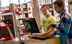 Twee jongens zoeken iets op in de catalogus in bib Permeke