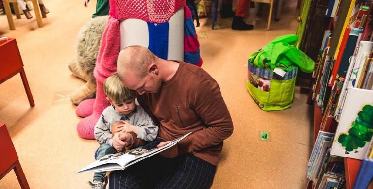 Een papa leest een verhaaltje voor aan zijn kind.