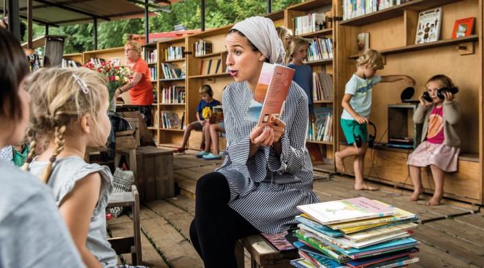 Vrijwilliger leest voor in open lucht
