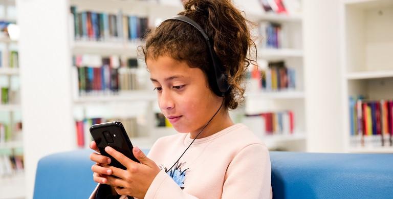 Meisje luistert naar een podcast in de bibliotheek