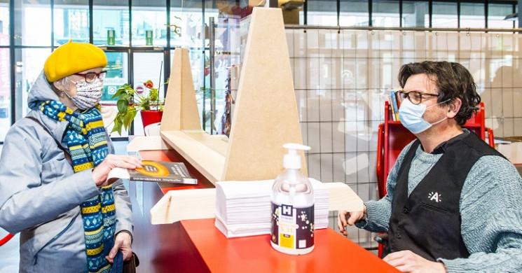 Vrouw haalt een boek af aan de balie van bib Permeke