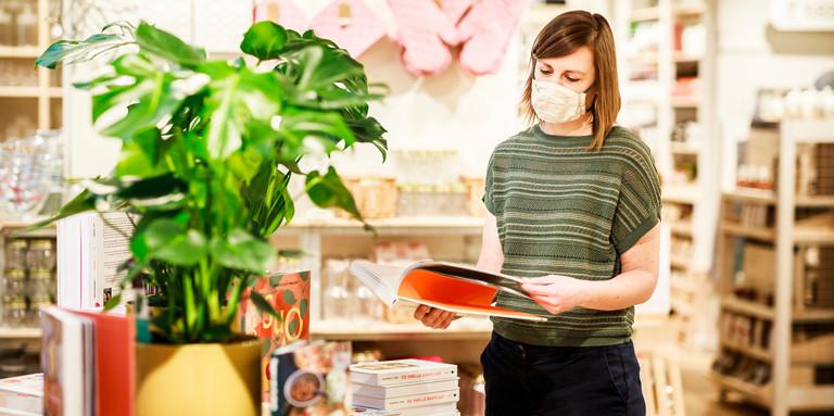 Vrouw met mondmasker kijkt in boek