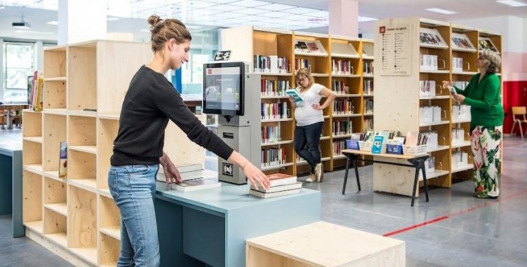 Een jonge vrouw leent materialen uit aan het zelfuitleentoestel. Op de achtergrond kiezen mensen boeken uit de rekken.