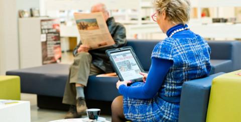 Vrouw leest de krant op een tablet van de bib