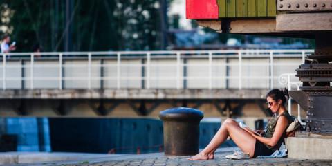 Vrouw zit te lezen aan de waterkant