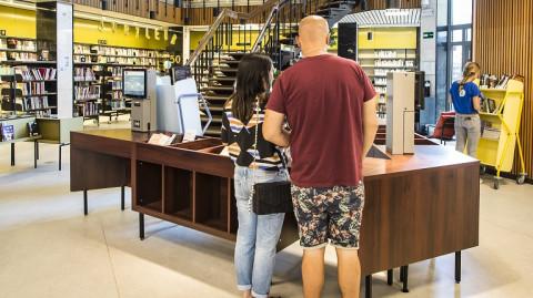 Man en vrouw scannen materialen in bib Driehoek