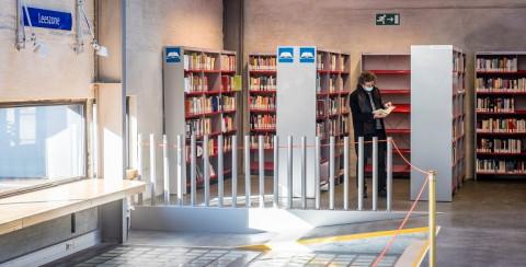 Tussen de boekenrekken in Permeke snuistert een dame met mondmasker in de boeken.